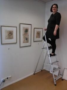 Nina Venäläinen ripustamassa näyttelyään